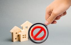 Magnifying glass is looking at the No Sign and the wooden house. Unavailability of housing, busy or low supply. Inaccessible royalty free stock photo