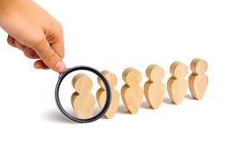 Magnifying glass is looking at the People stand in a formation on a white background. Discipline and order, submission. In anticipation of an order. People royalty free stock image