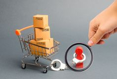 Magnifying glass is looking at a person is handcuffed to a bunch of boxes a on a supermarket cart. The concept of dependence on. Shopping and buying new things stock images
