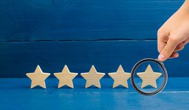 Magnifying glass is looking at the rating of the hotel, restaurant, mobile application.Five stars on a blue background. The concep. T of rating and evaluation royalty free stock images