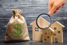 Magnifying glass is looking at the three houses near a bag with money. real estate acquisition and investment. royalty free stock image