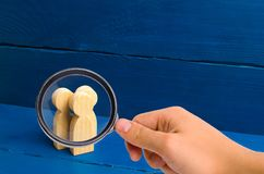 Magnifying glass is looking at the Three people stand together and talk. Three wooden figures of people conduct a conversation on. A blue background royalty free stock images