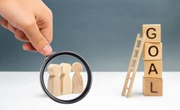 Magnifying glass is looking at a Three people are standing near the tower of cubes with the word goal royalty free stock photography