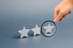Magnifying glass is looking at three stars on a gray background. The concept of rating and evaluation. The rating of the hotel royalty free stock photography