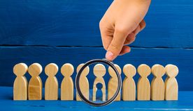 Magnifying glass is looking at the wooden figure of people with a void inside the body in the form of a child stands in line with stock photo
