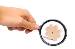 Magnifying glass is looking at the Wooden gear on a white background. Abstract background for presentations and banners. The concept of technology and industry royalty free stock images
