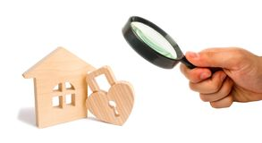 Magnifying glass is looking at the Wooden house with Heart shaped lock on a white background. Love nest, relationships. Buying a h. Ouse with a young family royalty free stock image