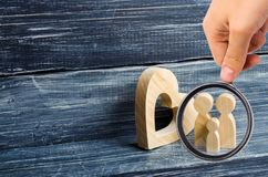 Magnifying glass is looking at the young family with a child is standing near a wooden heart. Love and loyalty stock images