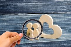 Magnifying glass is looking at the young family with a child is standing near a wooden heart. Love and loyalty, stock images