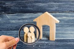 Magnifying glass is looking at the Young parents and a child are standing near their home. Concept real estate, buying stock photo