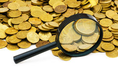Magnifying glass and lots of coins Stock Image