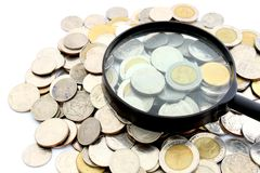 Magnifying glass and lots of gold coins Stock Photos