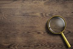 Magnifying glass or loupe on wooden table Royalty Free Stock Photos