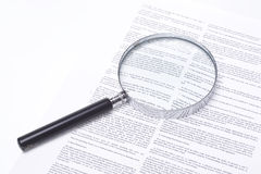 Magnifying glass lying on a legal contract. Still life showing a magnifying glass lying on a legal contract stock images