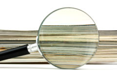 Magnifying glass and magazines Stock Photos