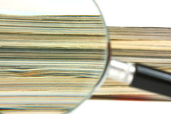 Magnifying glass and magazines Royalty Free Stock Photos