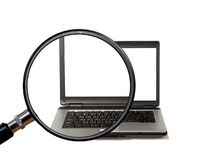 Magnifying glass magnifies laptop Stock Images
