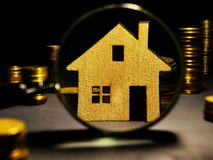 Magnifying glass and model of house. Property investment assessment stock photography
