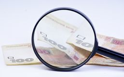 Magnifying glass with money Stock Image