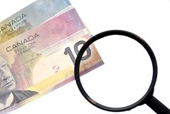 Magnifying glass on money background Stock Photos