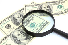 Magnifying glass on money background, Royalty Free Stock Photo