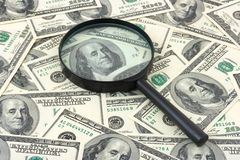 Magnifying glass on money background Stock Photo