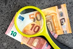 Magnifying glass and money euro isolated on stone background. Bancnots royalty free stock photo