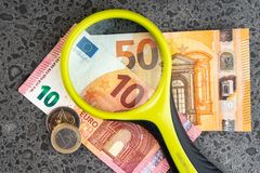 Magnifying glass and money euro isolated on stone background. Bancnots royalty free stock photography