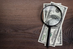 Magnifying glass and money on wooden background Stock Image