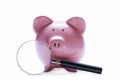 Magnifying glass next to a pink piggy bank Royalty Free Stock Photo