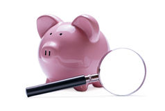 Magnifying glass next to a pink piggy bank Royalty Free Stock Photography