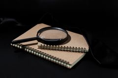 Magnifying glass and notebook on black background, investigate c. Oncept stock image