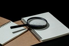 Magnifying glass and notebook on black background, investigate c. Oncept stock photo