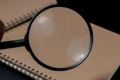 Magnifying glass and notebook on black background, investigate c. Oncept royalty free stock photos
