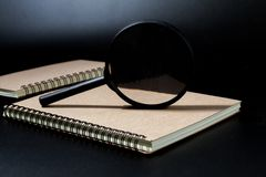 Magnifying glass and notebook on black background, investigate c. Oncept royalty free stock photography