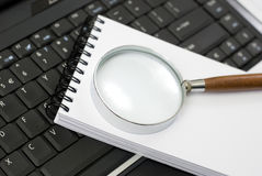 Magnifying glass on a notepad Royalty Free Stock Image