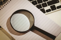 Magnifying glass and notepad on laptop Stock Photo