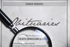 Magnifying glass and obituaries advertisement on newspaper Stock Photo