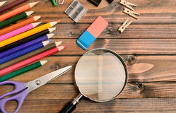 Magnifying glass with office supply Stock Photos