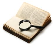 Magnifying glass and old book Stock Photos