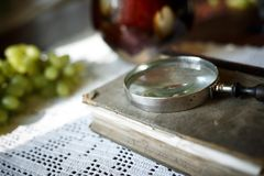 Magnifying glass and old book. Retro stylized photo. Selective focus stock photos