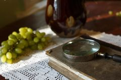 Magnifying glass and old book. Retro stylized photo. Selective focus stock images