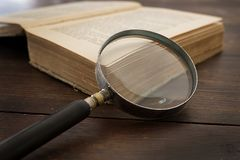 Magnifying glass and old book on old desk Royalty Free Stock Photos