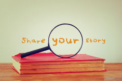 Magnifying glass , old book with the phrase share your story. filtered image. Magnifying glass , old book with the phrase share your story. filtered image Stock Photos