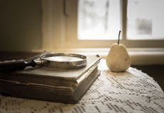 Magnifying glass and old book. Retro stylized photo. Selective focus stock image