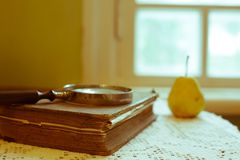 Magnifying glass and old book. Retro stylized photo. Selective focus stock photo