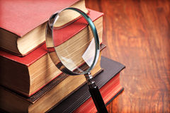 Magnifying glass with old books Royalty Free Stock Image