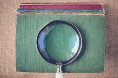 Magnifying Glass with old Books on Vintage Background with Insta Royalty Free Stock Photos