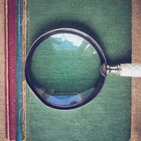 Magnifying Glass with old Books on Vintage Background with Insta Stock Photos