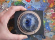 Magnifying glass on the old painting palette stock images